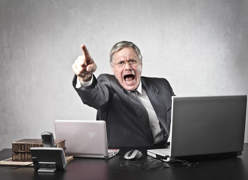 Man behind desk shouting