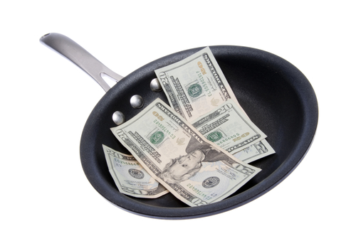 Money (dollar bills) in a Frying Pan to represent the cost of food, eating out, etc. Clipping path included with this file.