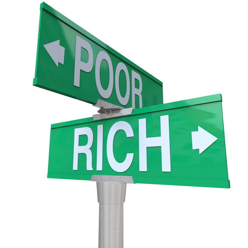 Rich vs Poor words on a green two way street or road signs pointing to poverty versus wealth to illustrate the difference between the opposites of haves and have-nots, separating the classes