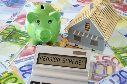 Pocket calculator with the words Pension Schemes on the display. Green Piggy Bank and a model of a new building on a background of Euro banknotes