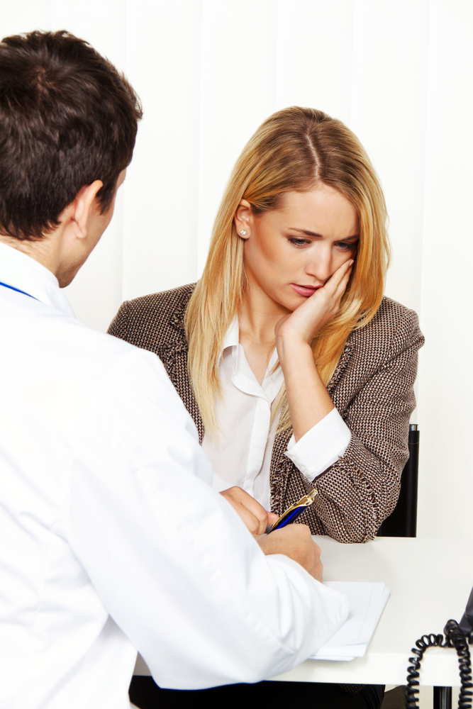 Woman looking sad talking to doctor
