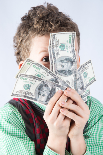 Boy holding a stack of hundred dollar bills