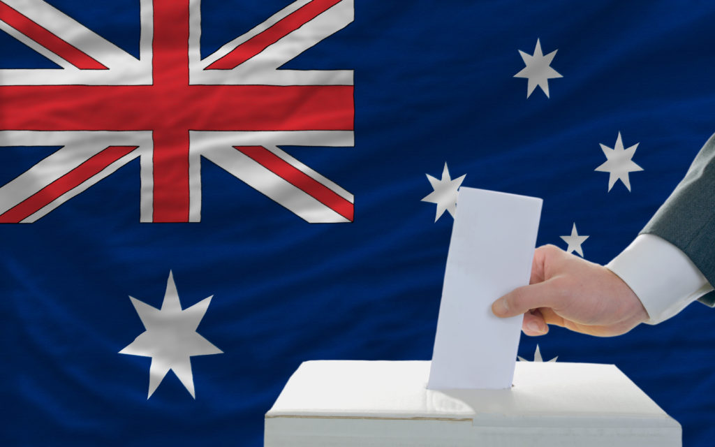man putting ballot in a box during elections in australia